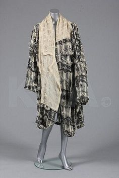 * Comme des Garçons 'beggar' coat, circa 1982-83, gold and black satin label, of loose, voluminous cut, open-weave wool in black and ivory with floating scarf-like lapel panels that attach at the hem, wide sleeves