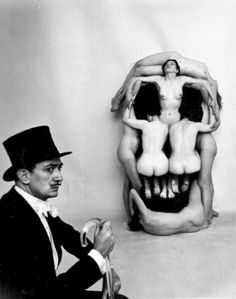 "In Voluptas Mors, portrait of Salvador Dalí posing beside a giant ""skull"", a tableau vivant comprising of seven nude female models. It was made in collaboration with Phillipe Halsman, 1951."