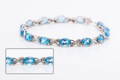 $649.99  Bracelet 10k en or blanc pèsent 8,8 grammes, sertie de diamants sur les mailles en X (entre les pierres ovales bleu).
