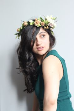 Her Wavy Hair frames her delicate face as she wears a Romantic Flower Crown.