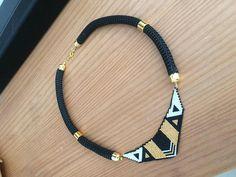 Collier plastron. Ce collier est tissé main, monté sur un cordon tressé noir 10mm, avec embout et poussoir de couleur doré. Il se ferme par des anneaux (donc réglable) et un fermoir de couleur doré. Une touche de blanc pour un coté neutre et illuminateur. Il est à la fois