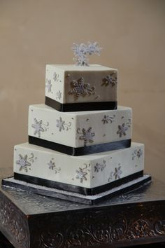 Three tier square Winter Wonderland wedding cake with black ribbon and silver snowflakes   One Fine Day Photography   villasiena.cc