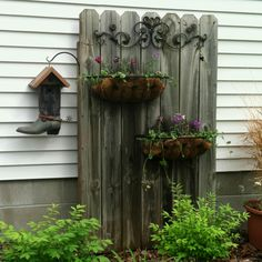 Old fence dressed up for outdoor decor - love the metal swirl hanger - half basket planters - nice place for a birdhouse too (and I love boot birdhouses) but a more traditional cottage-y birdhouse would be really cute here  ************************************************  (repin) #upcycle #fence #panel #outdoor #garden #decor