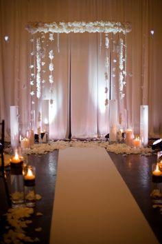 suspended arch with orchid garlands and lots of candle light