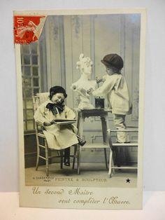 Cartolina postale di inizio '900: pittrice e scultore... sulla scritta in francese si legge: un secondo maestro vuole completare l'opera...