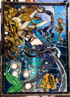 """Stained glass window with metal frame ready to be hung  Blues, greens, and amber tones, sea horse and fish design compliment a wide variety of decors   19"""" x  26"""""""