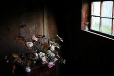 A vintage tin container of leafy plants and flowers by the window.