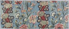 Small piece of chintz with a blue ground in a pattern of flowers in a perpendicular arrangement. White Sweet William with fantastic leaves in shades of green, yellow and red against a curving band of red alternates with groups of garden flowers: iris, asters, tiger lilies with foliage in shades of red, blue, yellow, sepia and green (blue over yellow).