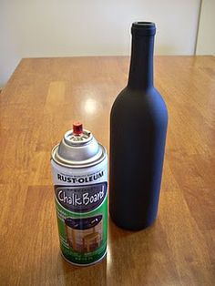 wine bottles sprayed with chalk board paint for table numbers; could go with the cork name tags