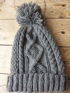 This quintessential Aran hat is perfect for keeping those heads toasty warm in the winter! This pattern is worked in the round and features a twisted knit rib, cables, diamond pattern, and double seed stitch. Decreases at the crown are worked so that the cable patterns continue to the top. The hat is topped with an optional pompom.