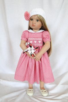 Sweethearts: A hand smocked dress for Kidz N Cats doll.    This sweet little dress is constructed from a creamy pink fabric with tiny white hearts. The hand smocking is done in white and pink floss featuring cable stacked hearts. The dress fastens in the back with two snaps. Back fabric tabs snap together and are decorated with a heart shape button. The bodice is self lined. The cap is hand crocheted with a cotton yarn and trimmed with a removable pink rosette. Also included is a Valentine…