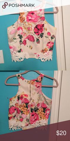 Colorful floral halter top Made from polyester. Colorful floral halter top. Includes a zipper in the back. White details on the bottom. Flowers are pink and yellow. The base color is off white. lulumari Tops