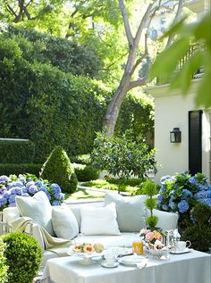 Lush patio with blue hydrangeas and a matching daybed and tablecloth on the cocktail table.