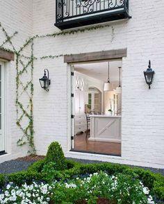White brick exterior with a pretty peek in to white kitchen