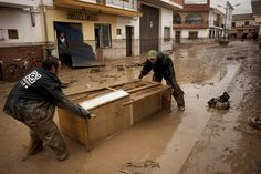 Two men pull a cupboard in the flooded streets of Villanueva del Trabuco, Spain. (Photo: Jorge Guerrero / AFP - Getty Image)