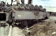 M113 APC upside down and being hooked up for recovery, 10th Cavalry, 1970.