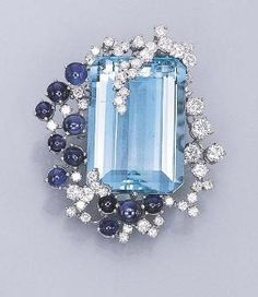 AN AQUAMARINE, SAPPHIRE AND DIAMOND CLIP BROOCH Set with a rectangular-cut aquamarine, held by overlapping circular-cut diamonds, to the circular-cut diamond and cabochon sapphire surround, mounted in 18k white gold by amelia