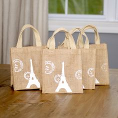 """This Eiffel Tower print burlap bag is perfect for that special gift. Great for use as a party favor or as a dinner party gift. - Color: White, Natural - Materials: Burlap - Dimensions: 6.5""""L x 6""""W x 4"""