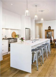 Love these glass pendants with the aluminum chairs and waterfall edge kitchen island