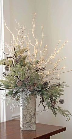Love this flower arrangement with the twig lights and nice muted greens...