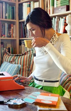 Sophisticated fashion doesn't have to be stuffy - White sweater with brown leather skinny belt, green skirt with wide pleats, multi layer necklace, bright desk accessories