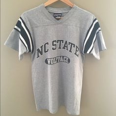 """Vintage NC State Varsity Style T-Shirt 90's varsity style gray NC State Wolfpack T-shirt. By Jansport. Sleeves feature black and white knit stripes.  Material of stripes resembles that of a standard beanie. Size Small. V-neck. Heavy weight cotton. Hang tag underneath Jansport tag is unreadable.   Length: 26.25"""" Width laid flat across chest: 18"""" Sleeve length: 8"""" Jansport Tops Tees - Short Sleeve"""
