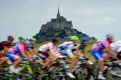 The peloton rides past the rocky tidal island of Mont Saint-Michel in the 226.5 km sixth stage of the 2011 Tour de France cycling race run between Dinan and Lisieux in northwestern France on July 7, 2011.