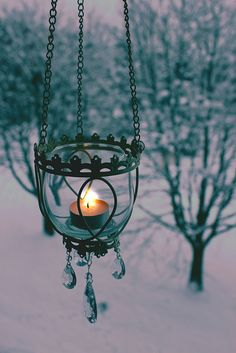 A winter's night in Oslo, Norway. Pretty hanging candle holder~glass, metal, crystals and candle light against a wintery backdrop.