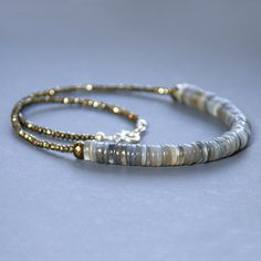 Gray Moonstone Tyre and Pyrite Choker    Delicate choker with a super sparkle!  This single strand necklace is made with tyre rondelles of gray moonstone that are paired with faceted roundels of pyrite. The center section with moonstone measures 5 inches and has a larger pyrite rondel on each side. This gemstone choker is finished with sterling silver findings. 16 inches long.      moonstone 2x7mm  pyrite 2.5mm      Thank you for looking! Please contact me if you have any questions or…