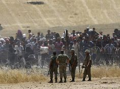 Turkish soldiers stand guard as Syrian refugees wait behind the border fences to cross into Turkey on the Turkish-Syrian border, near the southeastern town of Akcakale in Sanliurfa province, Turkey, June 5, 2015. REUTERS/Osman Orsal