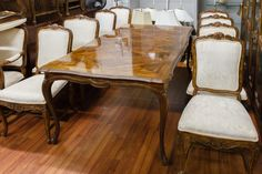 Lot 134: Burled Wood Dining Set by Drexel Heritage; Having a large table with two leaves and twelve chairs