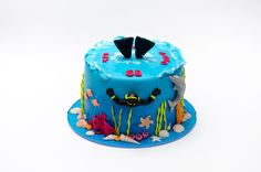 'Diver' ocean cake: about 4 layers, single tier, (looks it's) covered in fondant w/ shells, sea animals (including a cute dolphin), coral & plant life Also, diver mostly submerged. From gallery @ CakeCentral.com