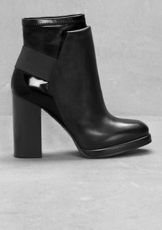 Classic ankle boots with updated details. A stacked leather heel is combined with stretchy nappa around the ankle with an over layering effect, and an elastic strap detail.
