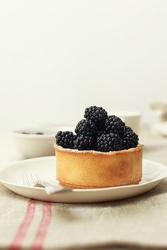 Lemon & lime tart with blackberries .