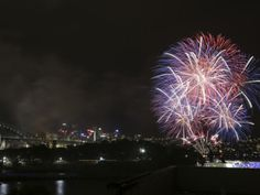 Fireworks explode near the Harbor Bridge and the Opera House during New Year's Eve celebrations in Sydney, Australia, Tuesday, Dec. 31,...