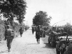 US troops on the road between Valognes and Cherbourg, 1944.