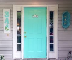 Turquoise | aqua beach house front door ideas - DIY mermaid house number sign - DIY beach house name sign with seahorse - cast iron crab door knocker painted white - Turquoise Front door and turquoise shutters painted with Pantone color systems Beach Glass. Turquoise, aqua, beach, beachy, blues and greens, coastal, scallop shells, exterior decorating ideas, exterior decor ideas