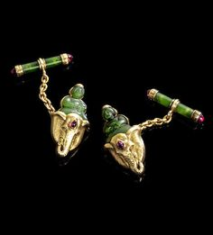 A pair of gold jewelled nephrite cufflinks by Fabergé, workmaster Alfred Thielemann, St. Petersburg, 1899-1908. Each link with seated nephrite figure surmounting elephant mask enriched at foreheads of each with cabochon rubies, connected by a gold-link chain to a nephrite bar with gold mounts terminating in further cabochon rubies.