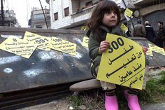 Education in Troubled Zones. A girl carries a sign that reads '300 children without education since two years' during a campaign organized by activists in the besieged area of Homs,