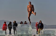 Credit: Sheng Li/Reuters A man jumps from an ice brick during a winter triathlon in Shenyang, China