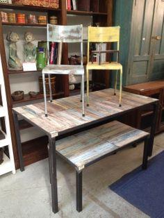 Tavolo con base di ferro e piano di legno di recupero colorato.