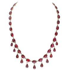 Breath catching pear shape garnets drop and sway from ovals that wrap the entire neck in luscious red, a color that is seductive on every woman. The setting for this Georgian delicacy is 15 kt gold. The garnets are set in gold cups with a foil inner backing. The clasp is original. Necklace is shown in original antique box. C. 1820