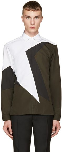 Long sleeve shirt colorblocked in olive green, black, and white. Panelled throughout. Spread collar. Buttoned fly front. Tonal stitching. Adjustable single-button barrel cuffs.