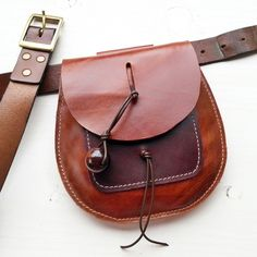 "Made in quality leather with rounded front flap. Its fairy perfect! A neat little bag to hang from your belt, just the right size for the essentials. Front mobile pocket. It closes nice and easily with a fairysteps big egg bead.DIMENSIONS: height - 18cms, width - 17cms, depth - will stretch with use, belt slot will fit a 2"" belt.*shown here on a 1 1/4"" belt to illustrate use*"