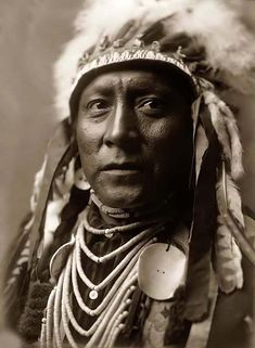 You are viewing an unusual image of Old White Man, a Crow Indian. It was taken in 1908 by Edward S. Curtis.    The image shows a Head-and-shoulders portrait of Crow Indian. The Indian is in traditional dress, with a War Bonnet