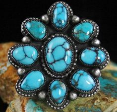 Sammie Kescoli Begay Gem Grade Candelaria Spiderweb Turquoise Cluster Ingot Ring | eBay  Nine perfectly matched rare gem grade natural turquoise cabochons from the Candelaria mine have been selected to create one of the finest known cluster rings. The gems are deep Candelaria blue with black and red webbing characteristic of the finest quality from this depleted claim in Nevada. The center stone is the focal piece and is striking in luster.