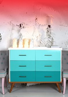 Ombre drawers, gray-teal-pink chairs, coral-red lighting...and I love that paper backdrop.
