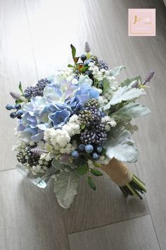 Bridal bouquet in hydrangea, baby's breath, berries and dusty millers