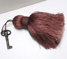 Extra Large Silky Tassel in rich wine and salmon shades. A rich embellishment for your antique furniture or hang on the door knob to your library. Coordinates well with traditional or todays popular Bohemian Decors. Handmade in India, with silky texture multi shades. Colors are Wine and Salmon peach. ****I have several of these, select another from the drop list ***Last pic is example of many other tassel styles at link below, NOT part of this listing. Listing is for: 1 extra large Tassel…