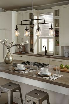 Influenced by the vintage industrial designs of early 20th Century America, the transitional Belton lighting collection by Sea Gull Lighting has Seeded glass shades that highlight the classic Edison bulbs. The assortment includes an island pendant as seen in this kitchen, plus chandeliers, a mini pendant, and bath fixtures.